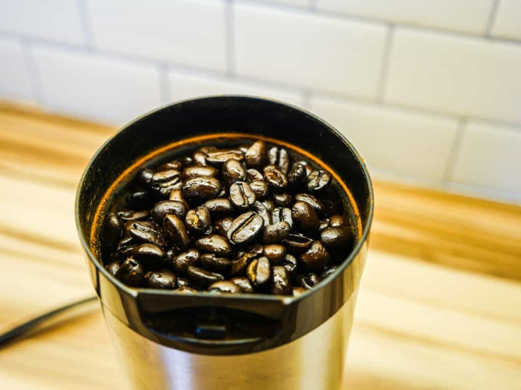 coffee grinder with whole beans in it